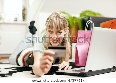 Woman lying in her home living room on floor shopping or doing banking transactions online in the Internet, emphasized by shopping bags in the background and her holding a credit card - stock photo