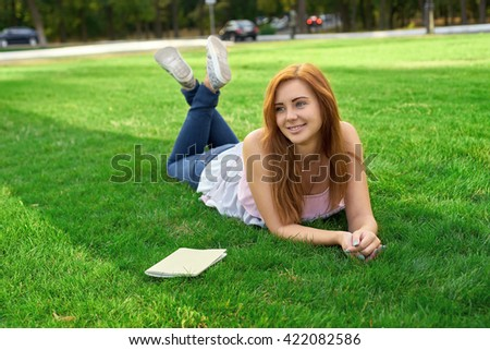 woman lying on a lawn with a diary