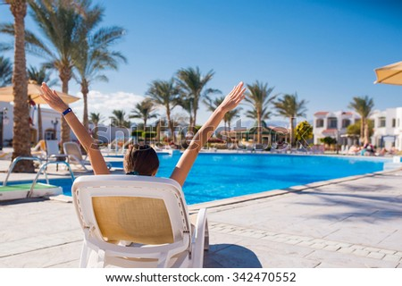 woman lying on a lounger by the pool. Relax on the sea - stock photo