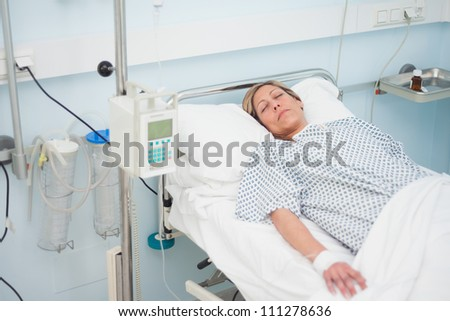 Woman lying on a medical bed with closed eyes in hospital ward - stock photo