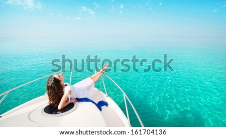 woman lying on a private yacht in the sea - stock photo