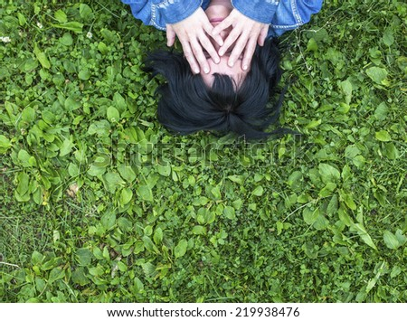 Woman lying on grass covering her face with her �¢??�¢??hands.  - stock photo
