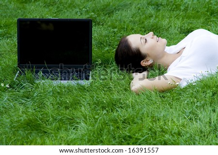 Woman lying on grass with laptop - stock photo