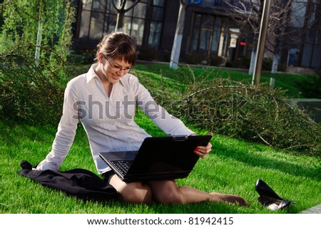 Woman lying on grass with laptop with business building on back - stock photo