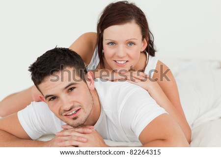 Woman lying on her man in the bedroom