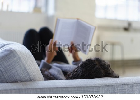 woman lying on her sofa reading a book, view over the shoulder - stock photo