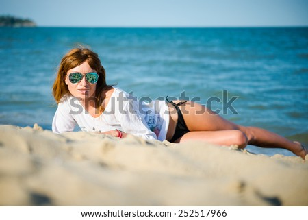 Woman lying on the beach sand. Beautiful Girl on The Beach. Travel and Vacation. Freedom Concept red-haired girl on the beach