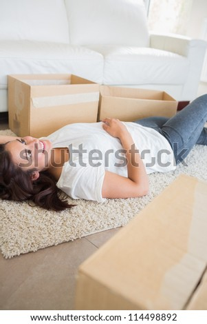 Woman lying on the carpet next to moving boxes in living room - stock photo
