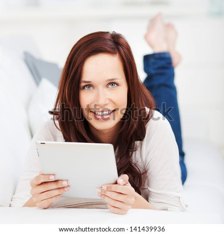Woman lying with a tablet on a sofa holding it in her hands and smiling at the camera - stock photo