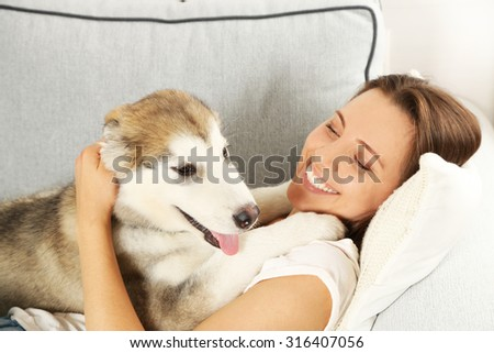 Woman lying with her malamute dog on sofa in room - stock photo