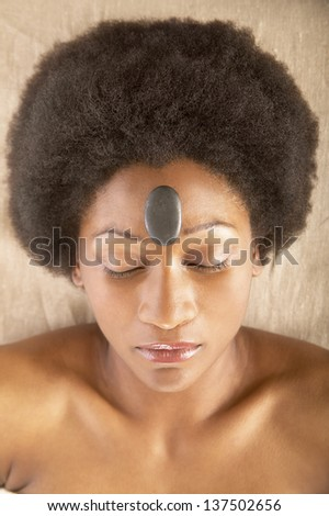 Woman lying with rock on forehead - stock photo