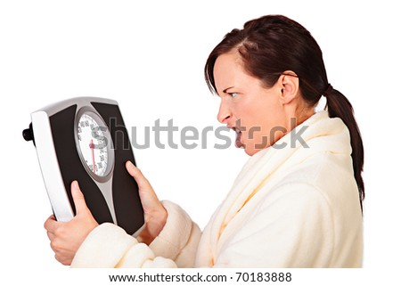 Woman mad at her scale shakes it - stock photo
