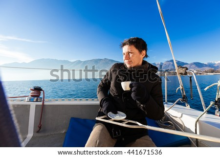 woman makes a coffee break aboard his sailboat