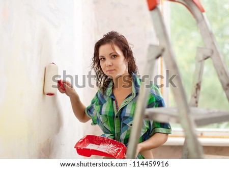 Woman makes repairs in the apartment - stock photo