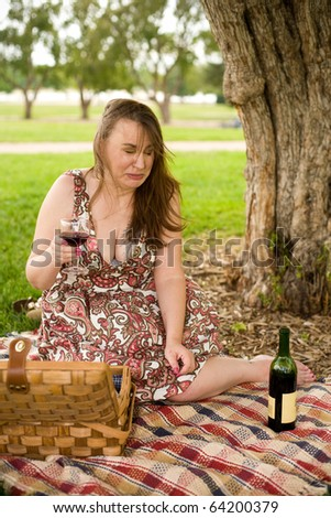 Woman making a face after sipping some bad wine on a picnic - stock photo