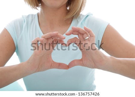 Woman making a heart gesture with her fingers in front of her chest, closeup cropped torso view of her hands