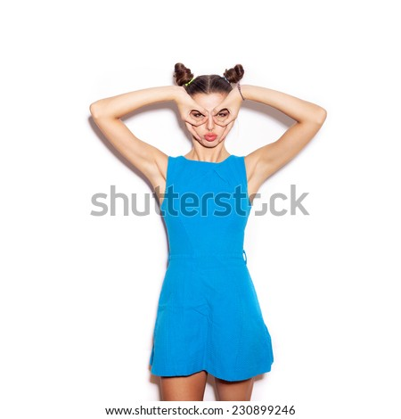 Woman making a pair of glasses with her hands. Beauty girl with bright makeup hairstyle with horns in a blue dress having fun. On a white background, not isolated - stock photo