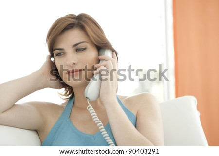 Woman making a phone call at home while sitting on a white sofa.