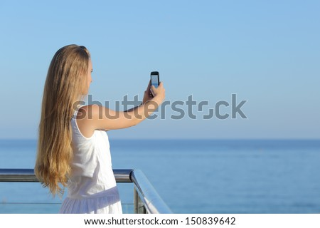 Woman making a photograph of the sea with a smart phone with the horizon over the sea in the background             - stock photo