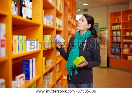 Woman making a product comparison in a drugstore - stock photo