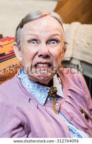 Woman making a scary face at the camera - stock photo