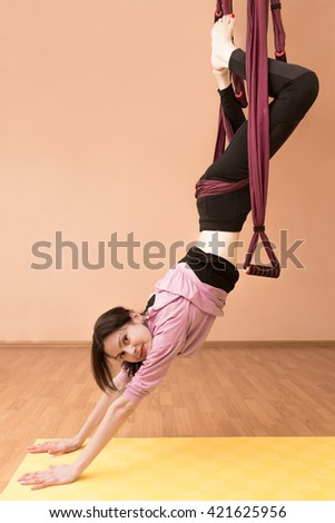 Woman making aerial yoga exercises, indoor, fly yoga