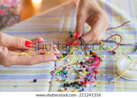 Woman making beaded bracelet with her hands