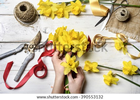 Woman making bouquet of narcissus - stock photo