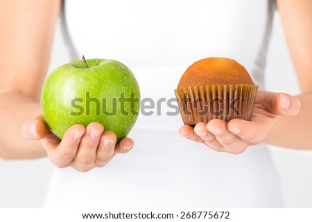 Woman making decision between healthy food or sweets. Dieting concept. - stock photo