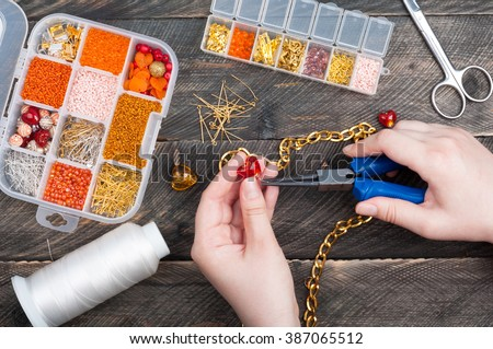 Woman making handmade jewellery. Handmade accessories. Box with beads, glass hearts, accessories for needlework on old wooden background. Top view - stock photo