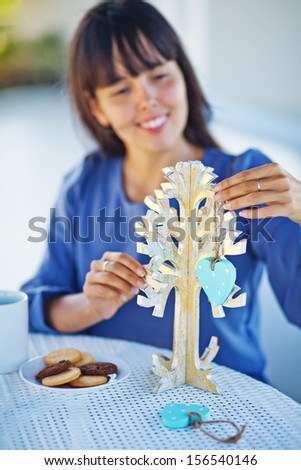 woman making handmade x-mas tree (soft focus on a tree) - stock photo