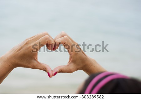 Woman making heart shape out of her hands looking towards the sea