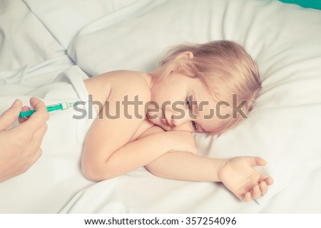 woman making injection by syringe in child hand - stock photo