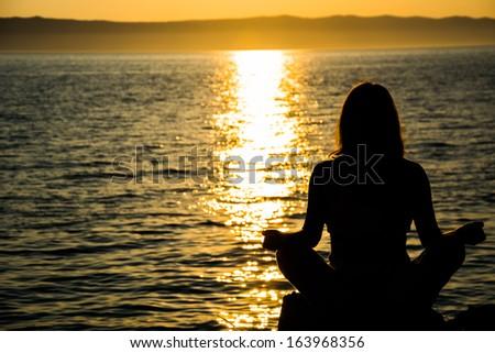 Woman making meditation at the sea - stock photo
