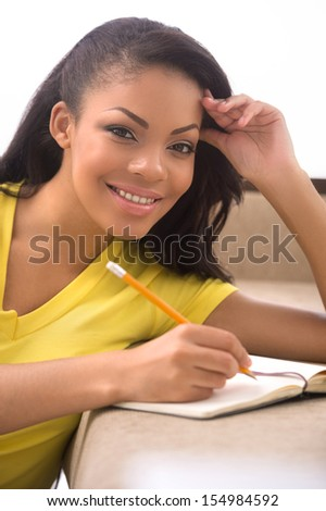 Woman making notes. Beautiful African descent women writing something in her note pad and looking at camera