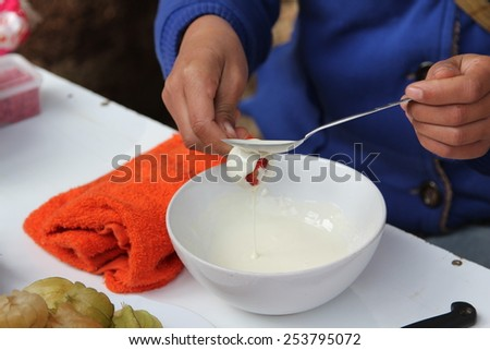 Woman making strawberry in white chocolate glaze. - stock photo