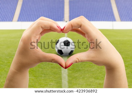woman making the heart shape with her hands because she loves football soccer - stock photo