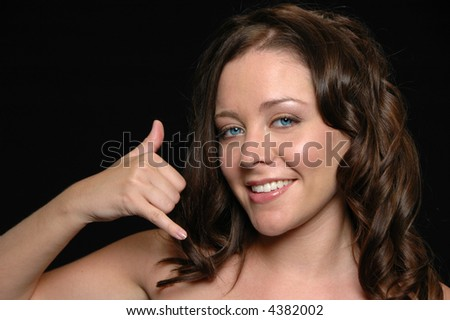 Woman making the  phone gesture against a black background - stock photo