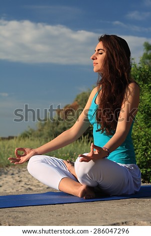 Woman making yoga figure on the beach at sunset - stock photo
