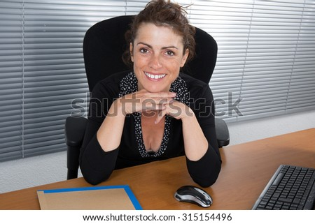 Woman, manager looking at the camera  at her work - stock photo