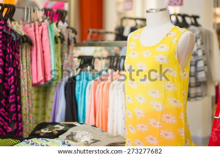 Woman mannequin in bright yellow flower pattern top and skirts with blouses on back - stock photo