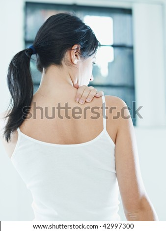 woman massaging neck. Rear view - stock photo