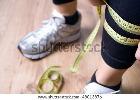 Woman measures a leg with centimeter after running at gym - stock photo