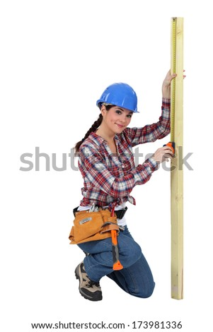 Woman measuring a piece of wood - stock photo