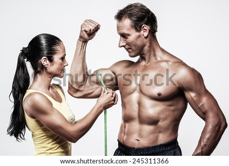 Woman measuring athletic's man biceps - stock photo