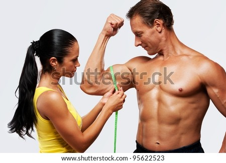 Woman measuring athletic's man biceps. - stock photo