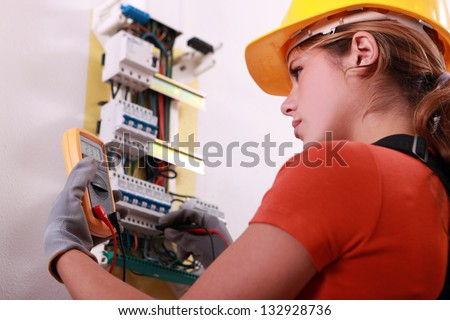 Woman measuring electrical current - stock photo