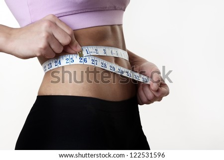 woman measuring her perfect shape body, healthy lifestyles concept - stock photo