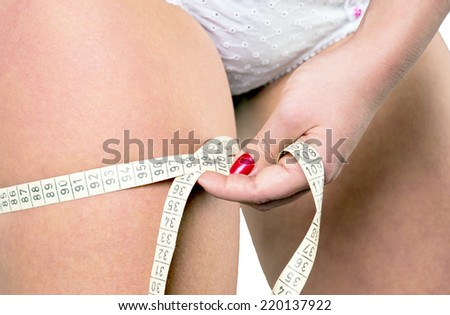 Woman measuring her thigh circumference / thigh circumference