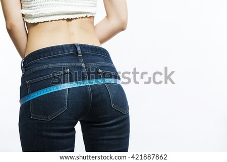 Woman measuring her waist with a blue measuring tape - stock photo